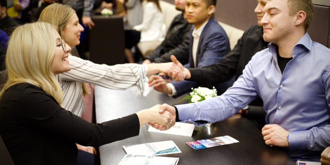 two people shake hands across a table