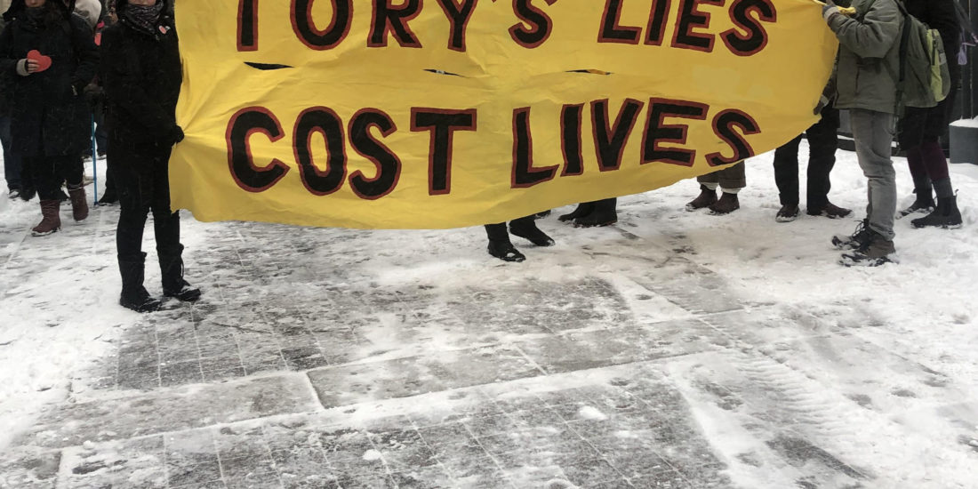 Marchers hold sign saying Tory's lies cost lives