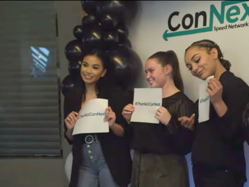 three people holding up connext signs and smiling