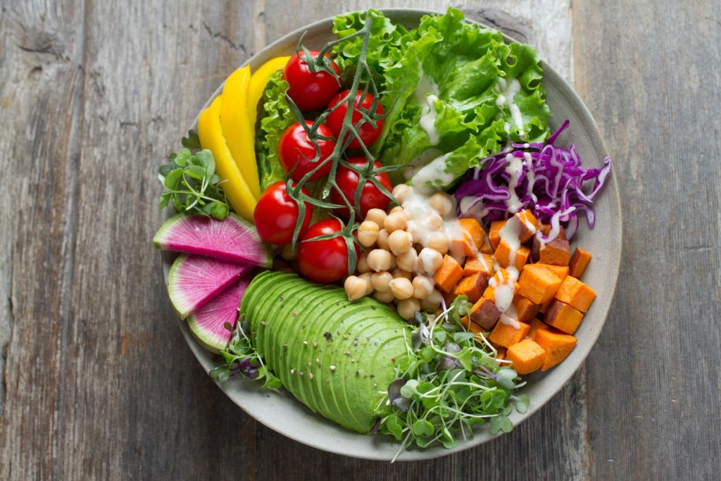 image of salad bowl including tomato, avocado, sweet potato, yellow peppers and more.
