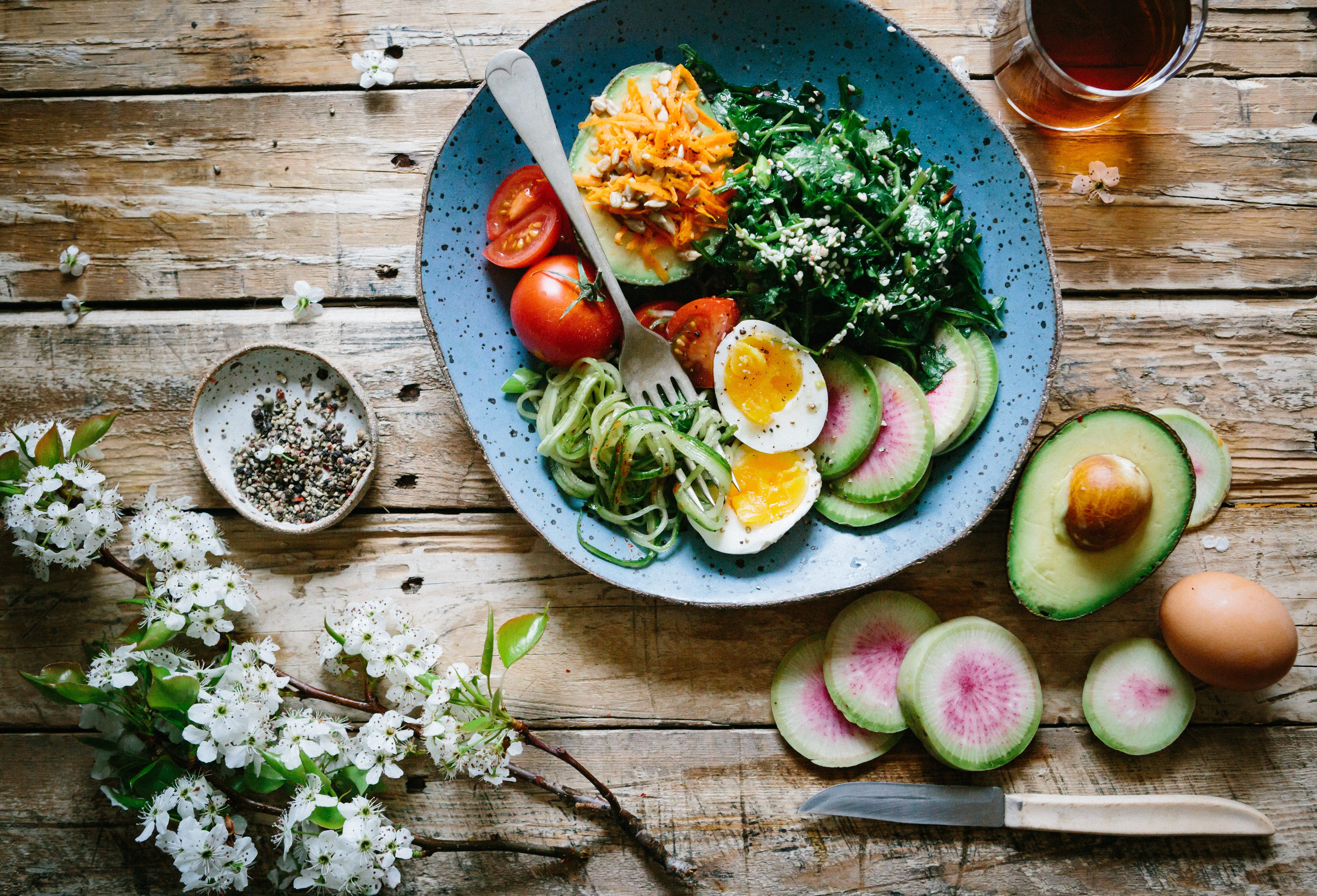 Image of blue ceramic bowl with eggs, spinach, avocado, tomatoes and cheese in it. Bowl is on wood counter, with cut up vegetables around it.