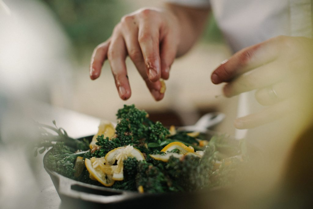 Image of cook putting lemons in rapini