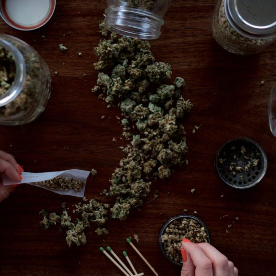 human hands above table with spilled cannabis jar, rolling joints with papers